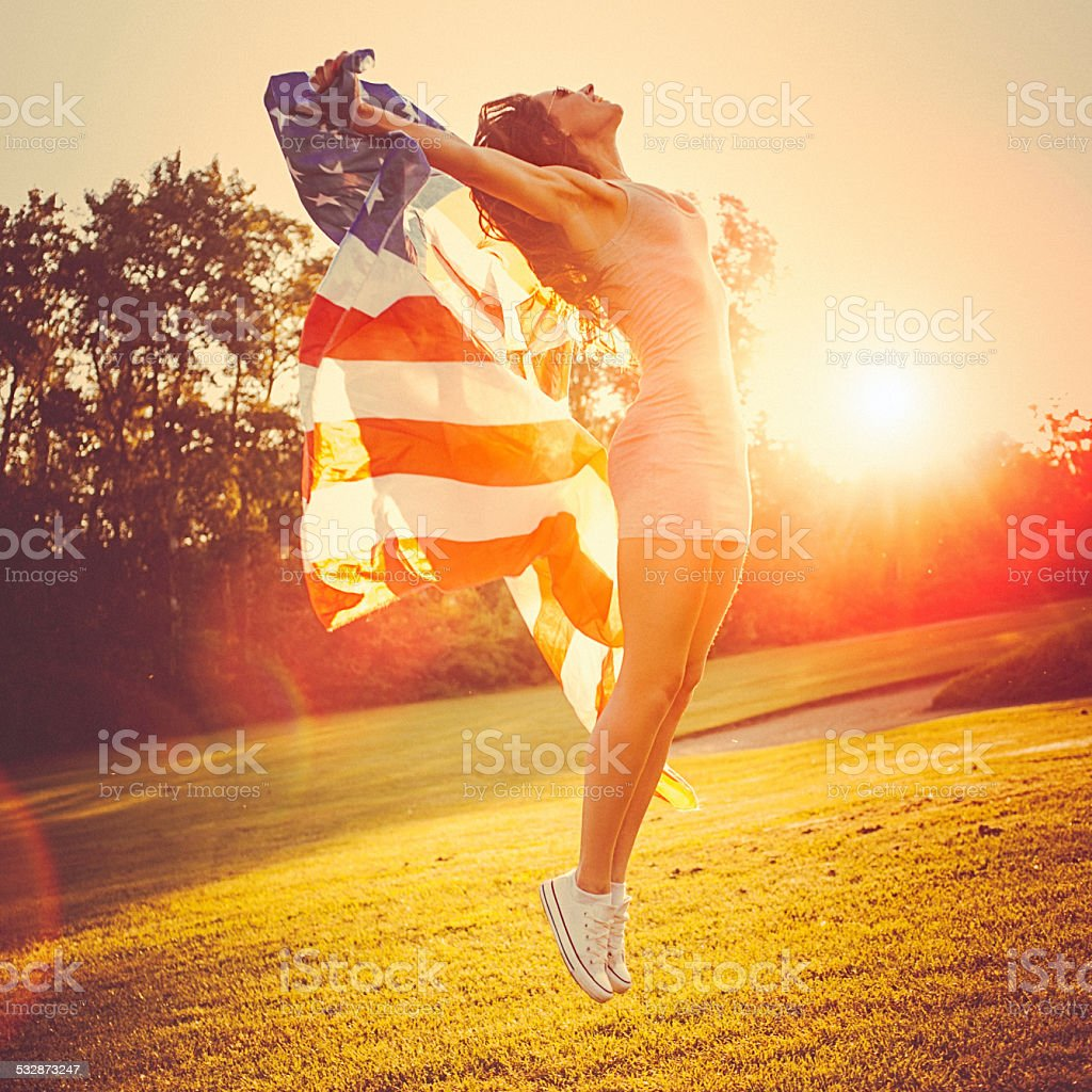 Young woman jumps in a meadow holding american flag stock photo