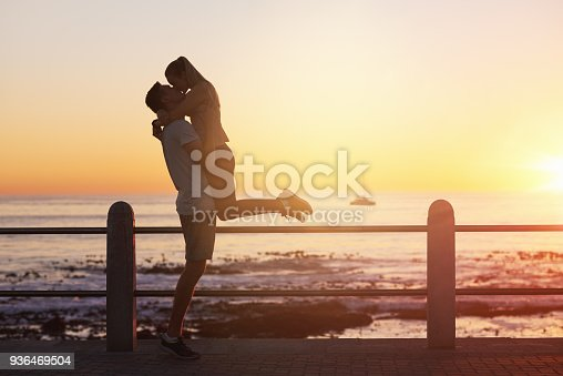 istock Young woman jumps into boyfriend's arms and gives him a kiss at sunset 936469504