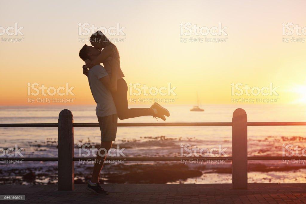 Junge Frau springt in die Arme des Freundes und gibt ihm einen Kuss bei Sonnenuntergang – Foto