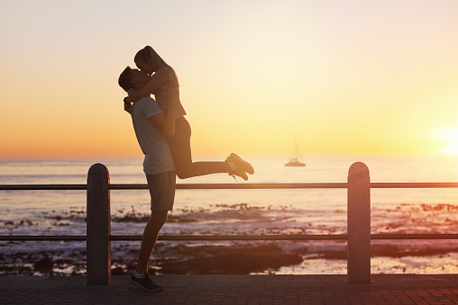 Young Woman Jumps Into Boyfriends Arms And Gives Him A Kiss At Sunset Stock Photo - Download Image Now