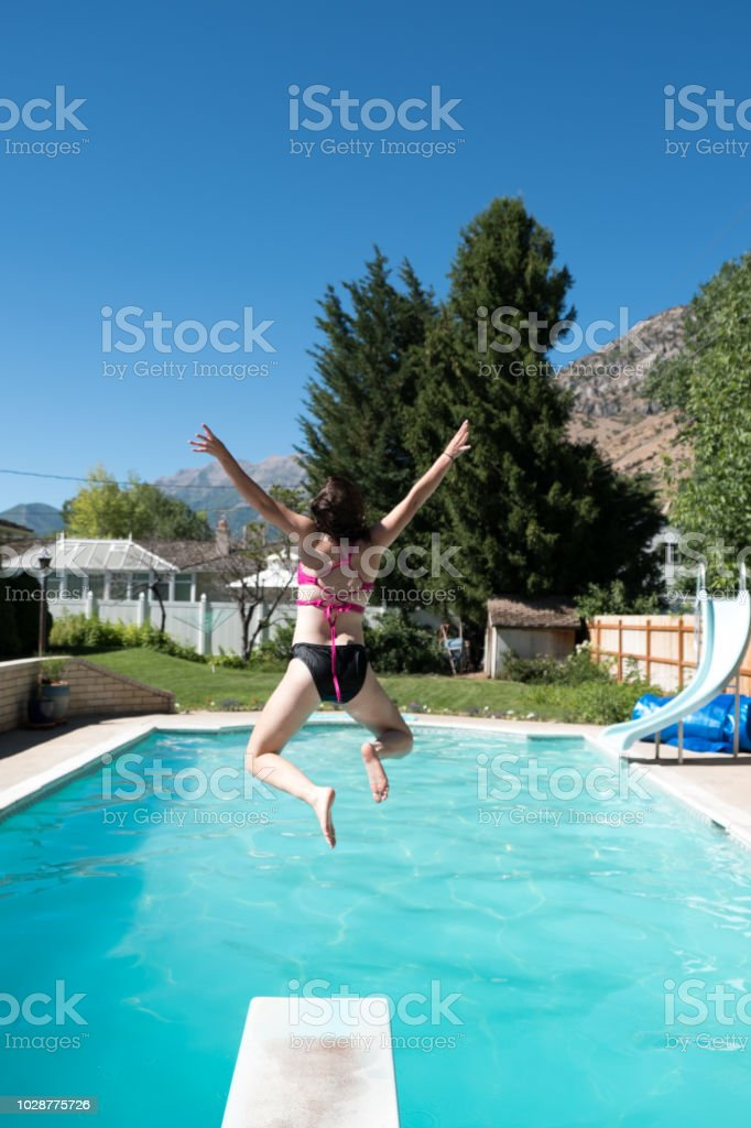 Young Woman Jumps Off Diving Board Into A Backyard Swimming ...