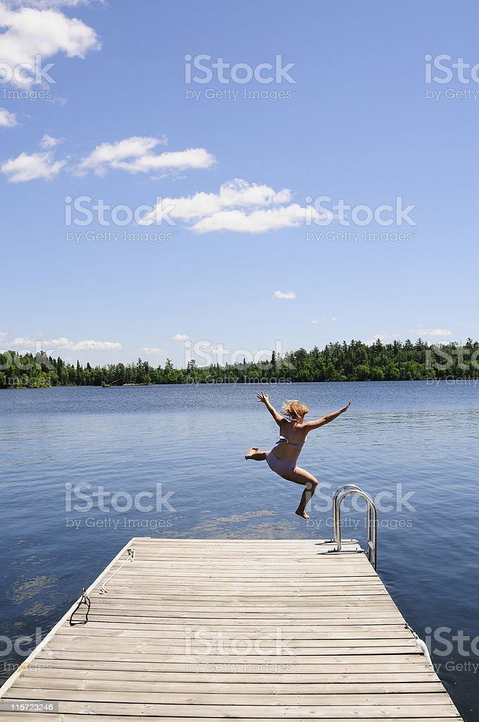 Young woman jumps off dock into lake perfect summer day. stock photo