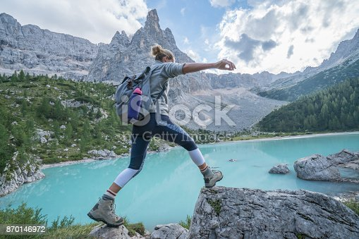 istock Young woman jumps rock to rock near mountain lake, Dolomites, Italy 870146972