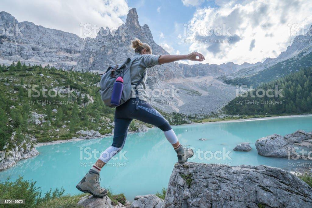 Junge Frau springt Fels zu Fels in der Nähe von Bergsee, Dolomiten, Italien – Foto