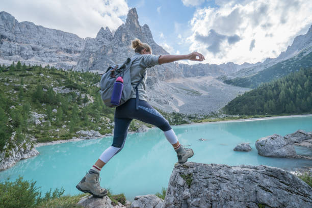 Young woman jumps rock to rock near mountain lake, Dolomites, Italy Young woman hiker jumping from rock to rock on mountain lake, Alto Adige, Dolomites, Italy stepping stock pictures, royalty-free photos & images