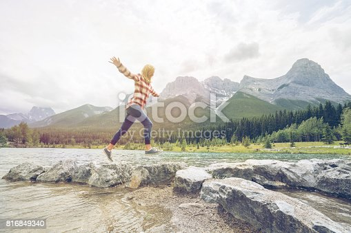 Young woman hiker jumping from rock to rock on mountain lake, Alberta, Canada