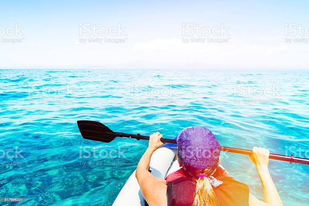 Young woman kayaking on open sea stock photo