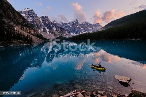 istock Young woman kayaks across mountain lake at sunrise 1227023176