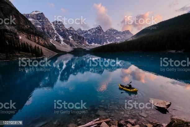 Photo of Young woman kayaks across mountain lake at sunrise