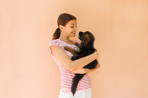 1149249445 istock photo Young woman keeping black German shepherd puppy near her face 1028302502