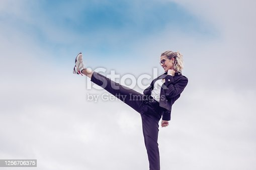 Young woman kicking as a sign of strength and addiction . In the background the blue sky. Kick it like a lady Concept.