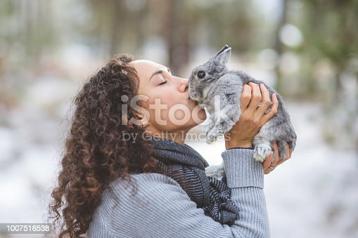 A young ethnic woman holds up her cute little bunny and kisses her. They're outside in the woods on a chilly winter afternoon.