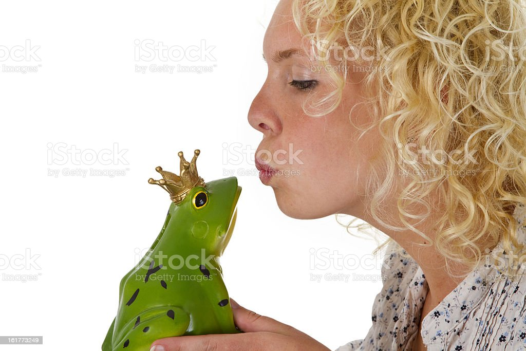 Young woman kissing a frog prince royalty-free stock photo