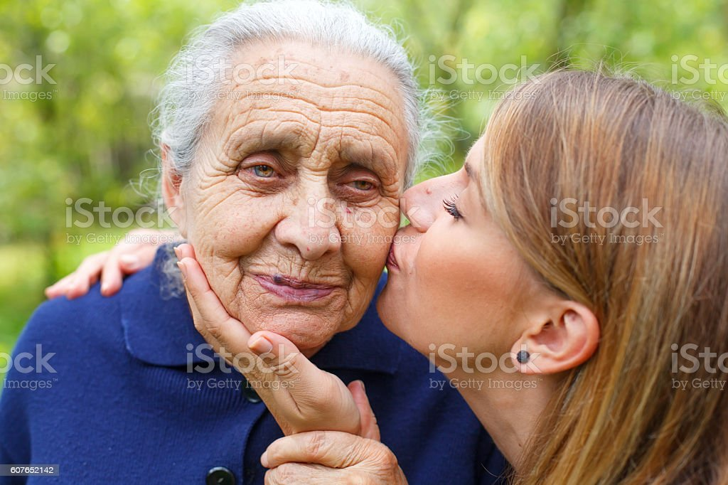 Young woman kissing her beautiful grandma stock photo