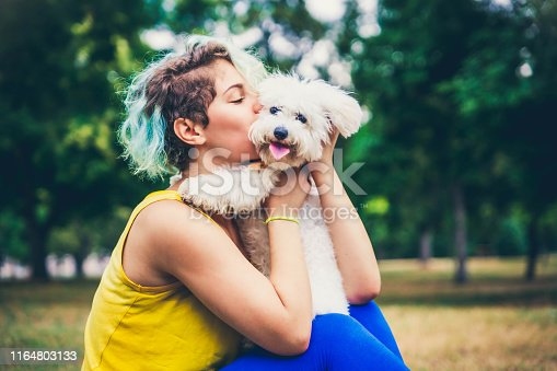 Young woman kissing her dog outdoors.