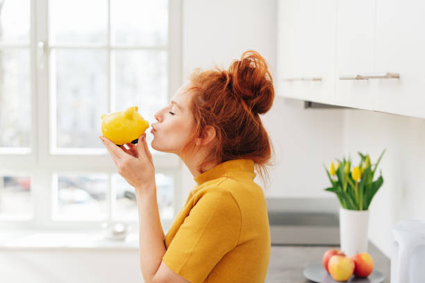 Young woman kissing piggy bank stock photo