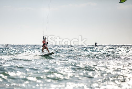 Young woman kiteboarding on the sea in summer day. Copy space.