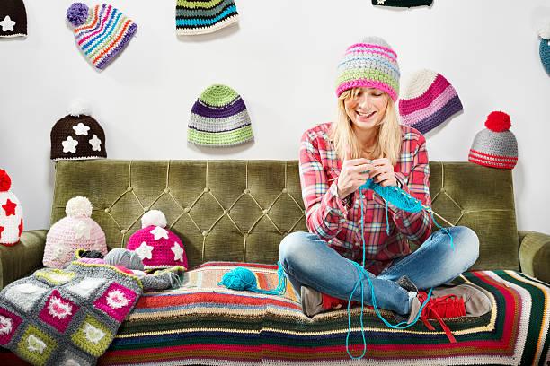 ragazza che lavora a maglia su divano con berretti invernali - lavorare a maglia foto e immagini stock