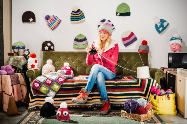 Young woman knitter portrait on couch with winter hats Young woman knitter portrait on couch with winter hats hobbies stock pictures, royalty-free photos & images