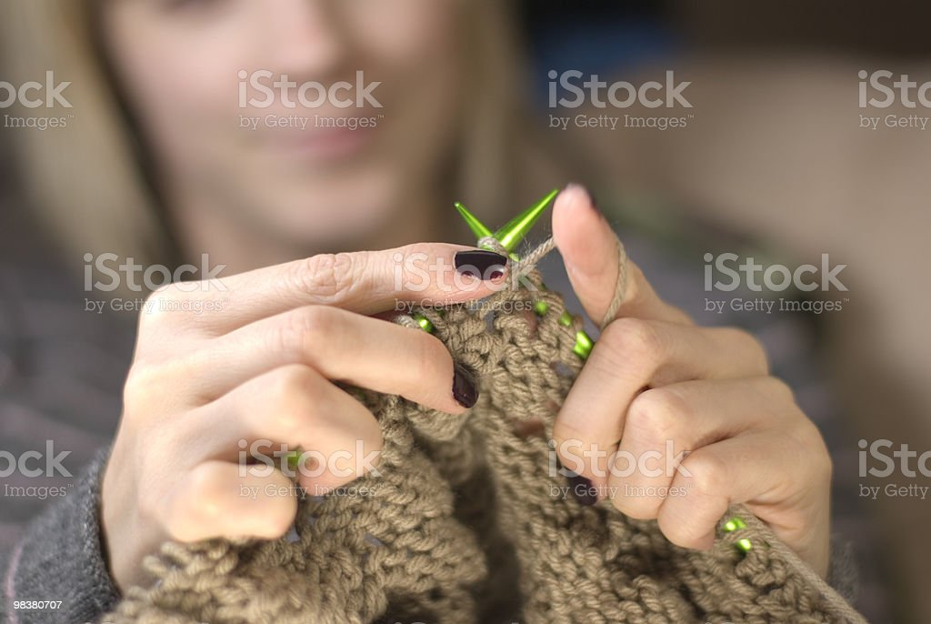 Young woman knitting a brown scarf with green needles royalty-free stock photo