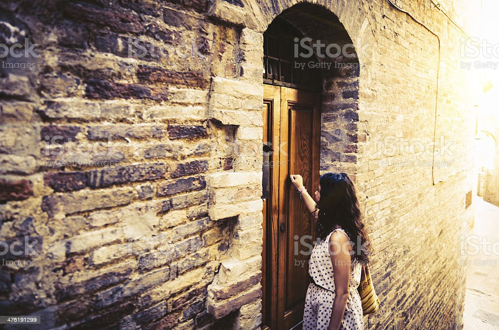Young woman knocks on the door of an ancient building stock photo