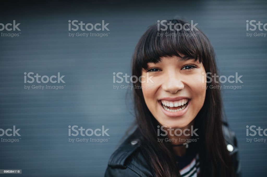 Young woman laughing against gray background royalty-free stock photo