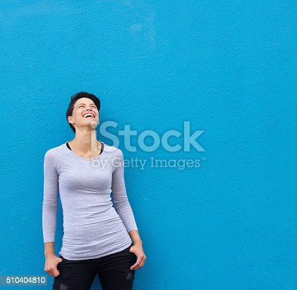istock Young woman laughing and looking up 510404810