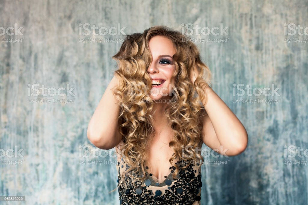 Young Woman Laughing. Pretty Female Model with Long Curly Hair