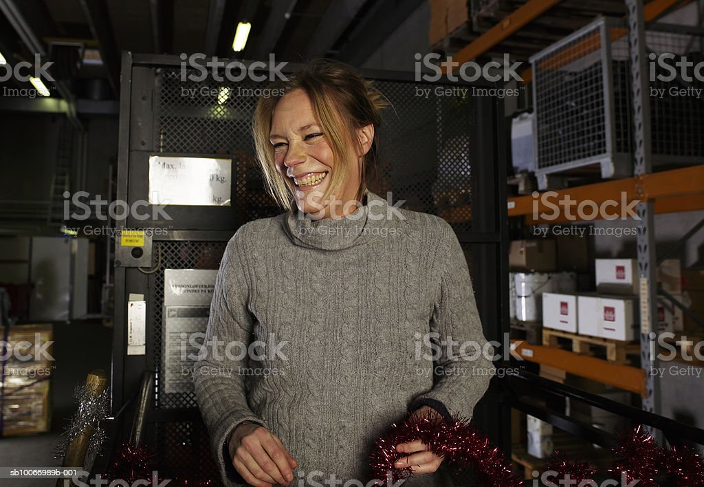 Young woman laughing, standing in warehouse holding tassle royalty-free stock photo