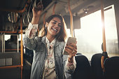 Young woman wearing earphones laughing at a text message on her cellphone while riding on a bus