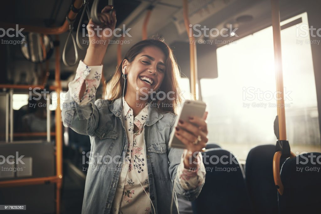 Young woman laughing while listening to music on a bus stock photo