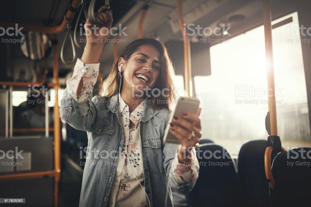 Junge Frau beim Musikhören auf einem Bus lachen – Foto