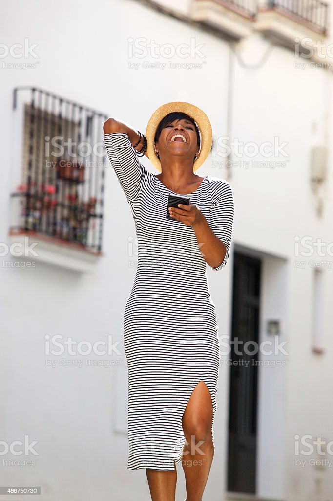 Young woman laughing with cell phone stock photo