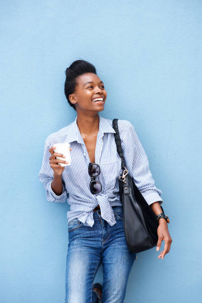 jovem mulher rindo com a xícara de café e bolsa contra parede - lifestyle color background - fotografias e filmes do acervo