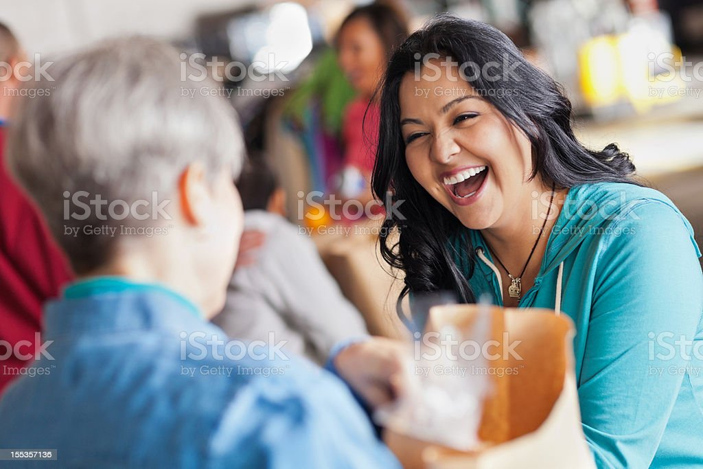 Young woman laughing with someone while handling food royalty-free stock photo