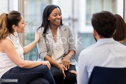 956725746 istock photo Young woman laughs during group therapy 1142334506