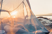 Young woman lying down in her tent at sunrise on a beautiful summer morning