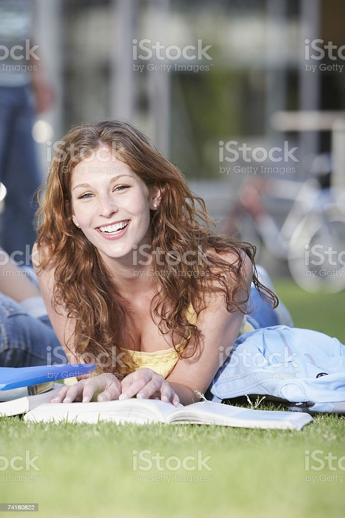 Young woman laying down on grass with books royalty-free stock photo