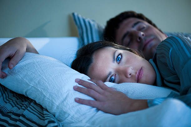 Young woman laying in bed with her eyes open stock photo