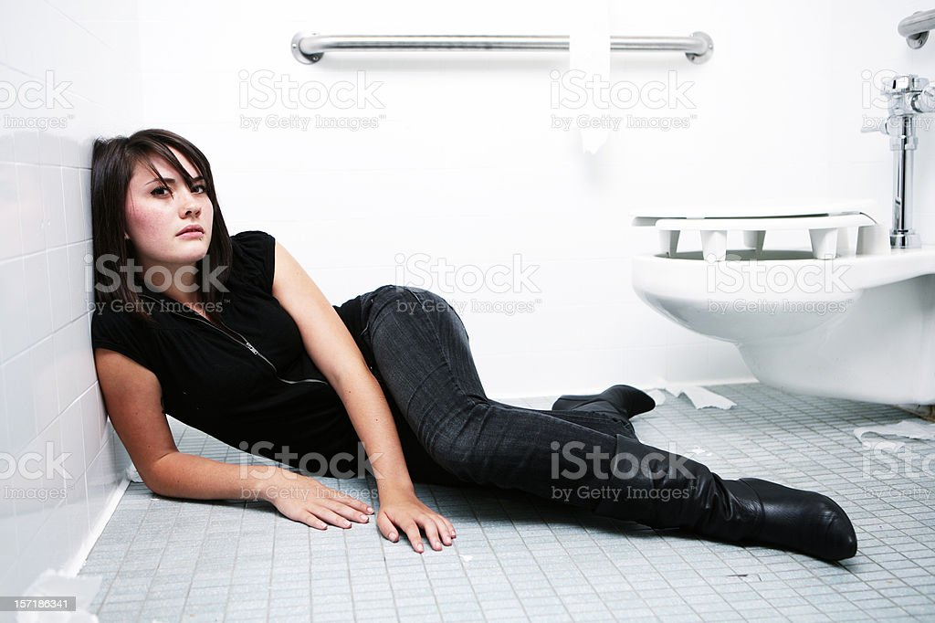 Young Woman Laying On Bathroom Floor WIth Helpless Expression. royalty-free stock photo