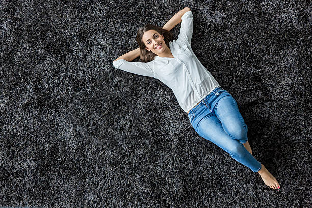 Young woman laying on the carpet圖像檔