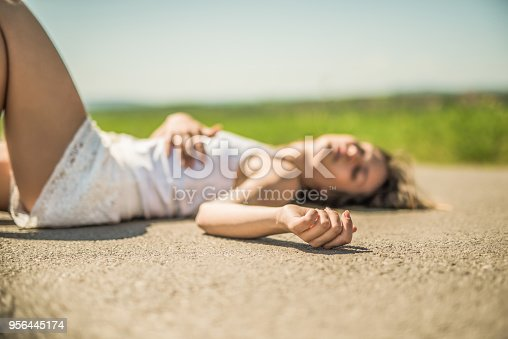 istock Young woman laying on the road after a car accident. 956445174