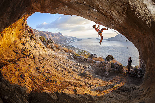 jovem mulher levar escalada na cave, ciclistas de alpinista de ancoragem - escalação em rocha - fotografias e filmes do acervo