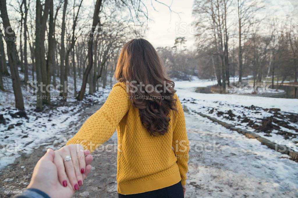 Young woman leading man stock photo