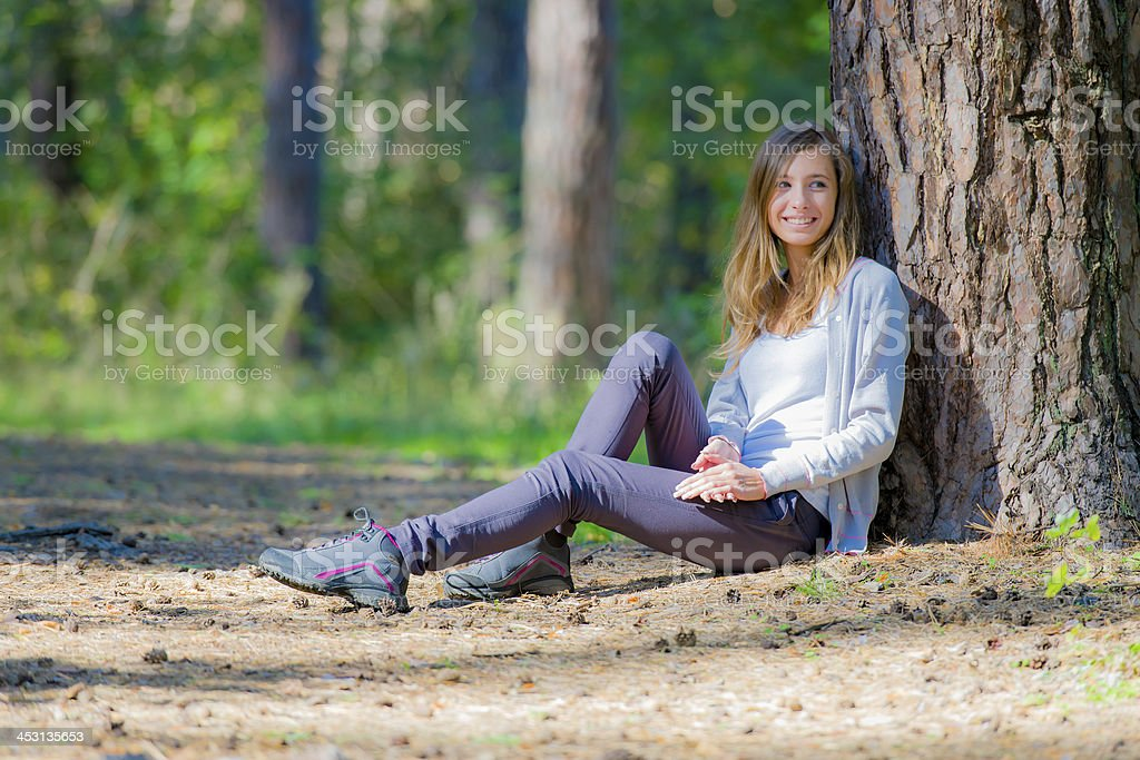 Молодая женщина, откинулся назад на дерево стоковое фото