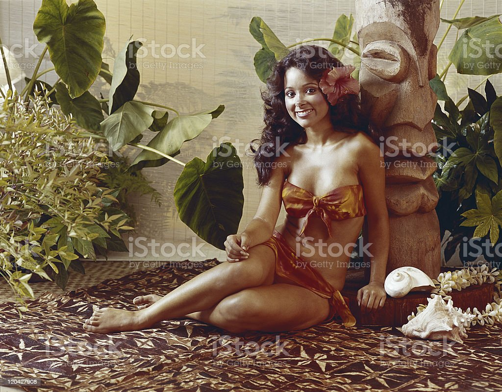 Young woman leaning against totem pole, smiling, portrait stock photo
