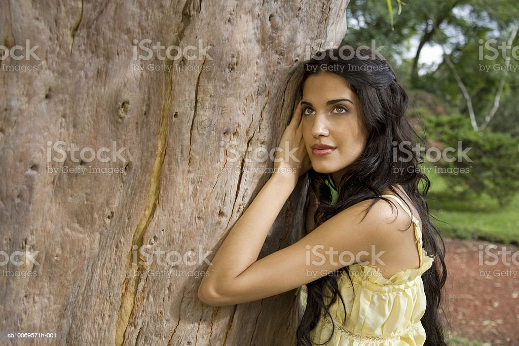 Young woman leaning against tree in park foto de stock libre de derechos