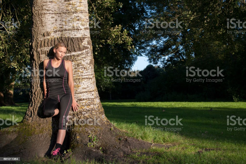 young woman leaning against tree in park to cool down after running royalty-free stock photo