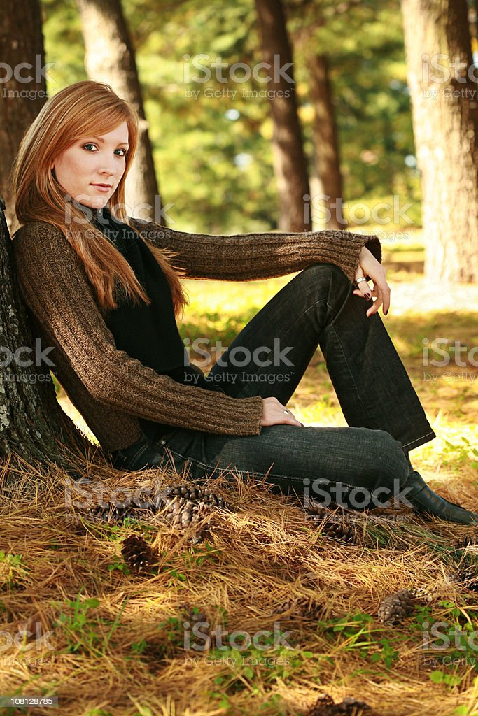 Young Woman Leaning Against Tree stock photo