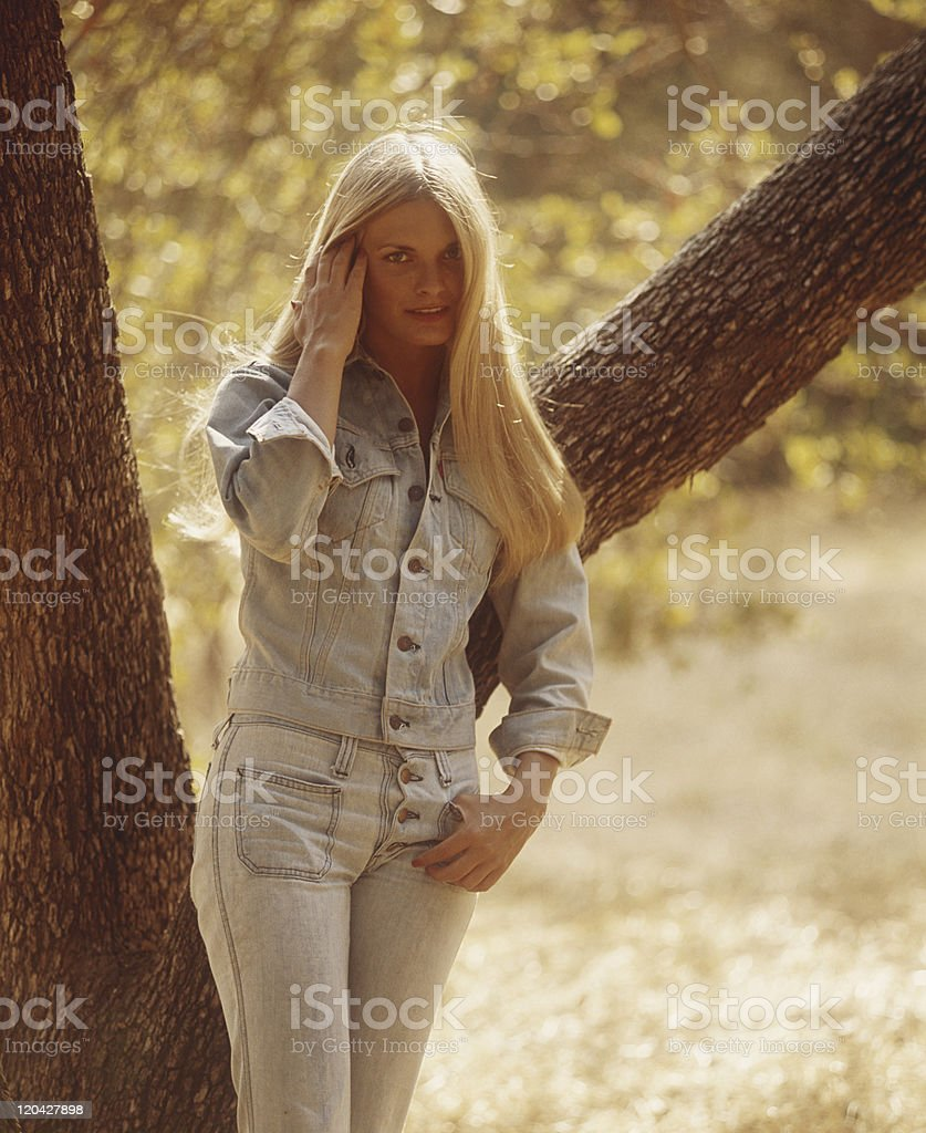 Young woman leaning against tree, portrait stock photo